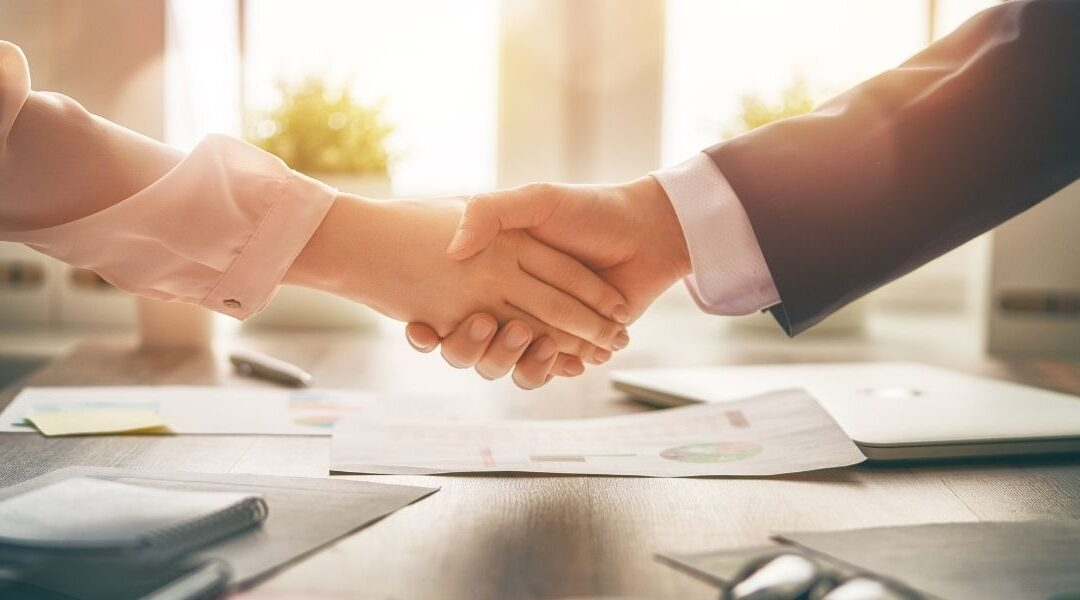 A handshake representing two alternative dispute resolution firms merger